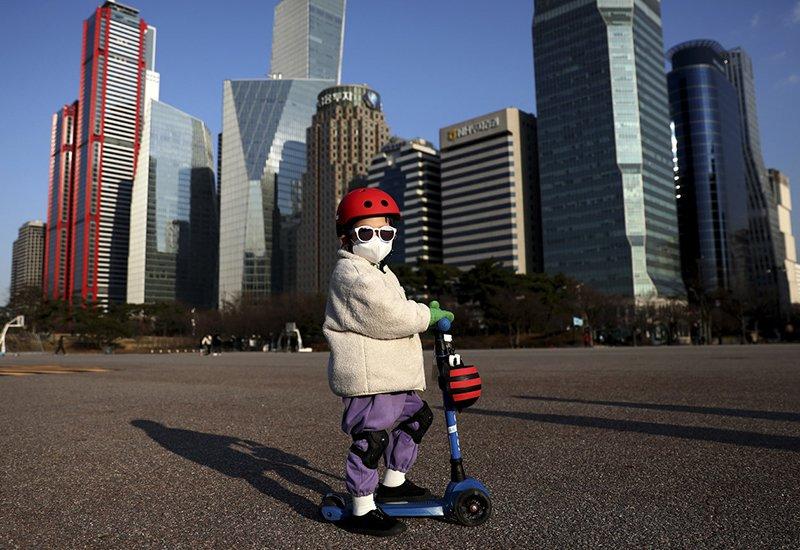 Một em bé đeo khẩu trang kín mít, chạy xescooter trên đường phố Seoul, Hàn Quốc.