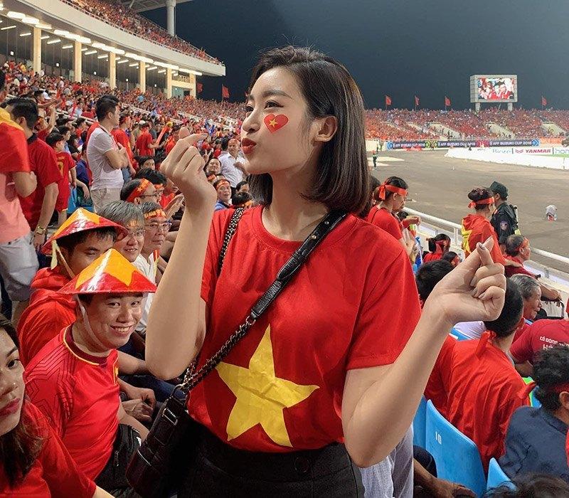 Hoa hậu Đỗ Mỹ Linh khai màn cổ vũ với bức ảnh diện áo cờ đỏ sao vàng mix kèm quần jeans đen, cô xách thêm túi Chanel lúc đi xem ĐT Việt Nam còn đá trong thời buổi chưa có dịch bệnh để động viên các cầu thủ.